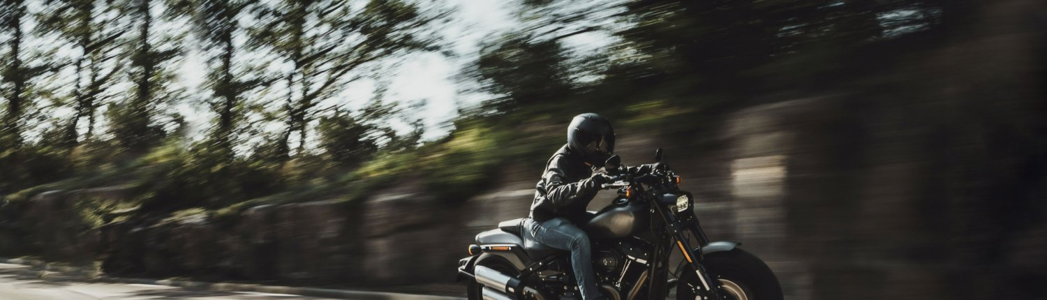 A man on a motorcycle is on a ride, covered by Aegis Powersports F&I products.